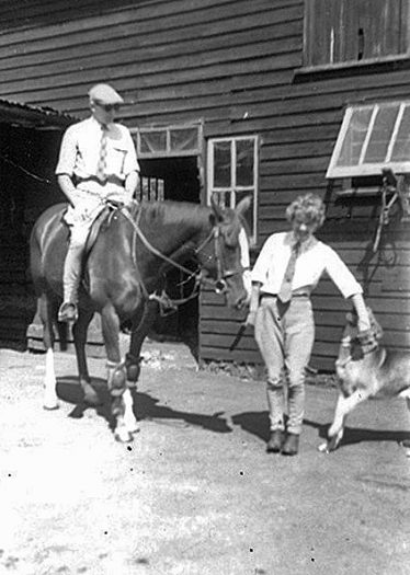 Mr Christopher on Miss Fabian, Mrs Christopher to the right being 'played with' by their German Shepherd dog Prince. Door to the long stable and the alleyway past the feed room visible in the background. | Jill Pakenham
