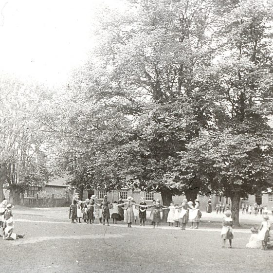 Girls playing on the Common outside the British School (seen through the trees) - now Park Hall, 1890s | LHS archives, cat.no. B 1.58