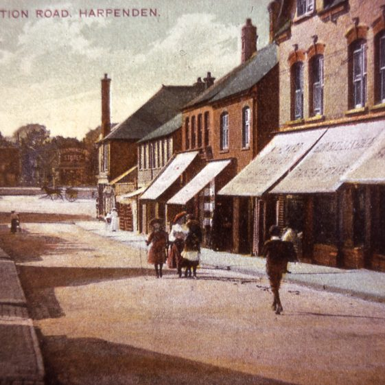 Station Road, shops on north side, looking west. Tinted postcard - 1910's | Cat no Slides B 2.47