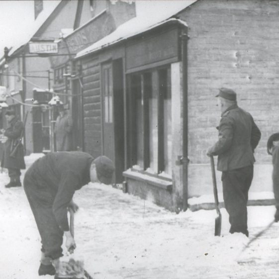PoW's clearing snow outside Thurston's Studio in the High Street - 1940's.  Click on the photo for more information about the PoW camp at Batford | Cat no Slides B 2.56
