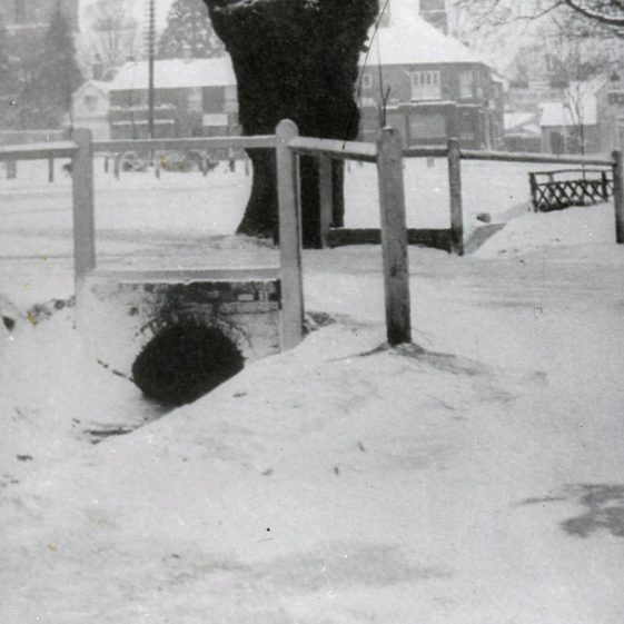 High St with view over Church Green and Cock Inn on right- snow - bridge over ditches 1900's | Cat no Slides B 2.57