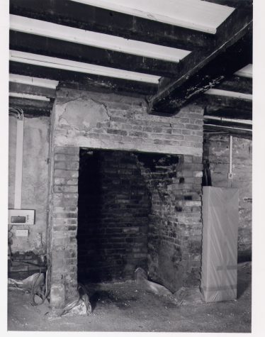 2 Southdown Road - Hall, lower (N) end with C19 brick hearth and the spine beam of the floor inserted in the C17, chamfered and stopped against the chimney. | RCHM 1975