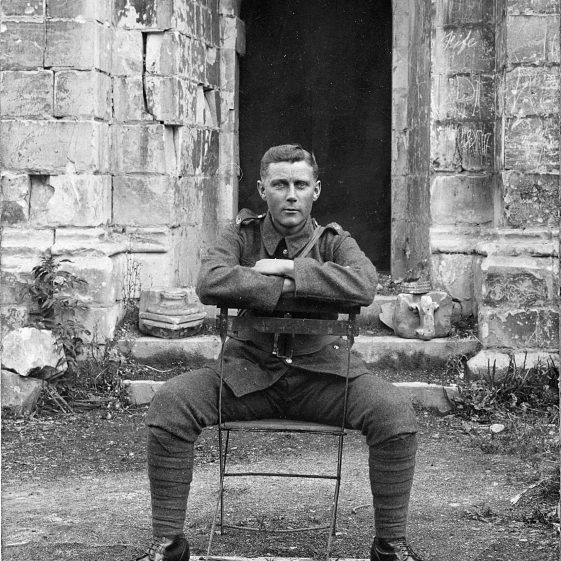 8.  Bertie Weston (?), on a camp stool outside the side door of a ruined church.  Inscription on the back: Arras Cathedral, 1917 | Di Castle's family albums