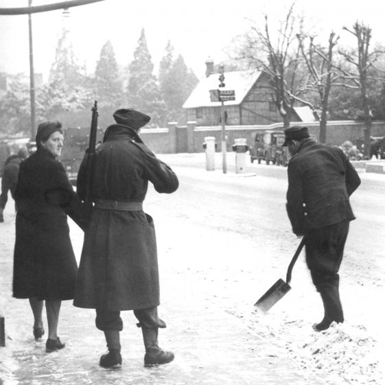 POW clearing snow with armed guard looking towards Sun Lane - 1940's | Cat no HC 88