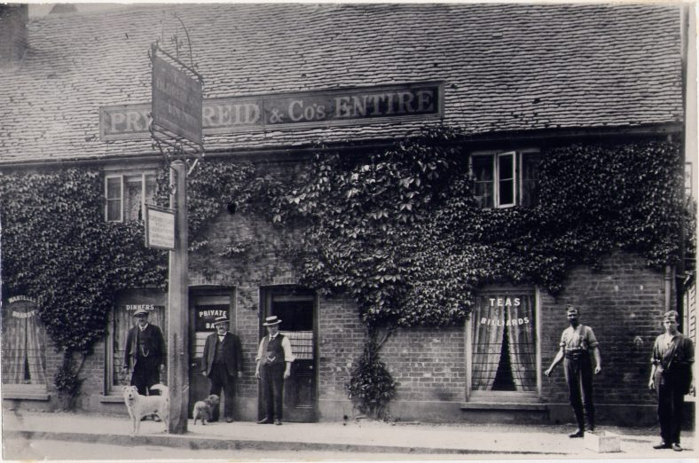 The Old Red Lion, 72 High Street.  An inn from the 18th century, when it was used for manor court business for Westminster Abbey.  When St Nicholas church school was being rebuilt in 1864, classes were held in the clubroom.  It closed in 1920, and became Reads cycle repair shop.  It was refurbished in 1976.  The left-hand part is now Billy's Bar, with Fine fitted Interiors at the right-hand end. | LHS collection, c. 1900