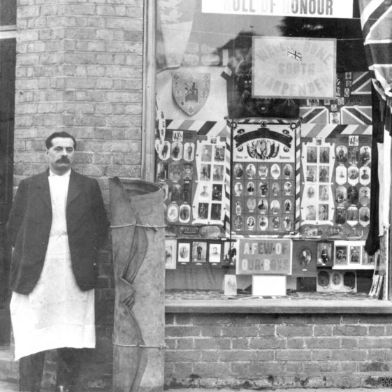 Frederick Thurston's photo of Mr Timson outside his shop with a Roll of Honour of South Harpenden men, 1919